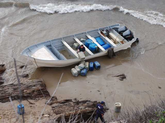 Law enforcement personnel remove evidence from a panga boat that came ashore between Gaviota and El Capitan state beaches in Santa Barbara County on Wednesday.