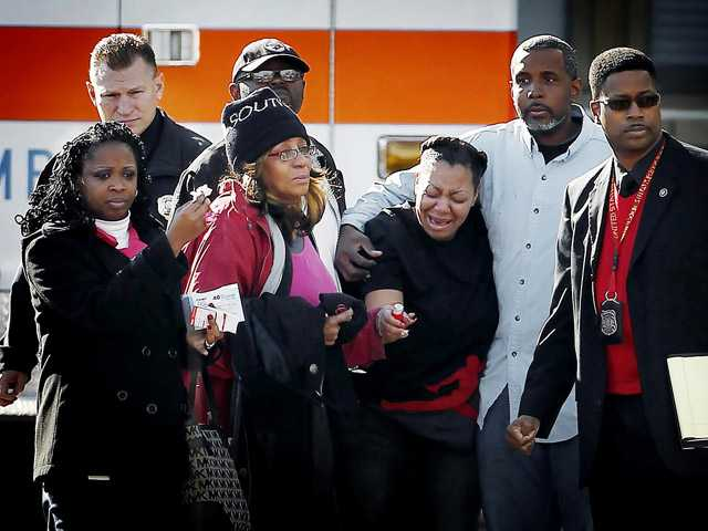 Mourners gather at the Regional Medical Center after a police officer was fatally shot and another wounded during a shootout Friday in Memphis, Tenn.