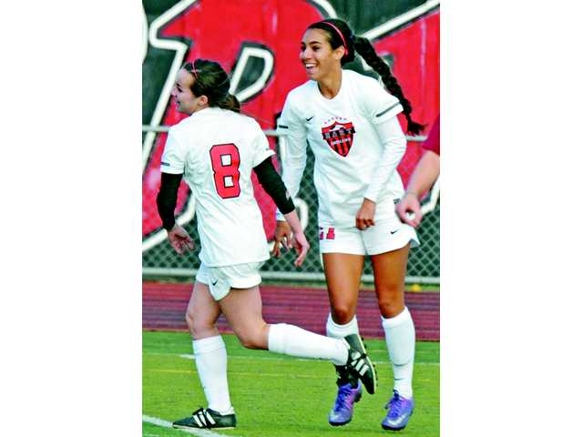 Hart's Ally Perez, right, and McKinley Kane celebrate Perez's first goal at Hart High on Thursday. The Indians earned their first win of the season.