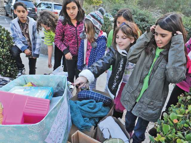 Bella Cario, 9, second right, and Cora Sweeney, 10, right, discuss the contents of 10 boxes gathered by students in the Roots & Shoots program, which were donated to the shelter on Thursday.