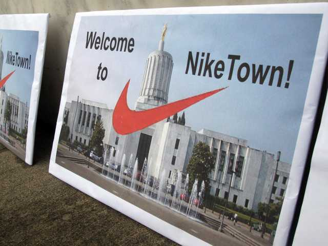 Signs protesting emergency legislation requested by apparel giant Nike Inc., greet visitors arriving at the Oregon state Capitol in Salem, Ore., on Friday.