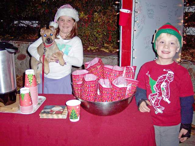 Emma Tisdell, 8 1/2, left holds Buddy, a rescue puppy as brother Spencer, 6, passes out popcorn to the judges during the annual Holiday Light Tour judging evening.
