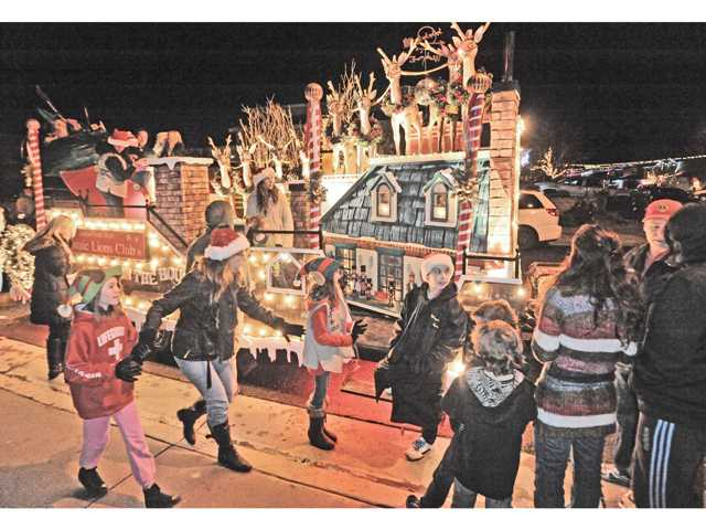 A line forms as people wait for a photo with Santa on the Castaic Lions Club Santa Claus Christmas float as it makes a stop on San Remo Place in Castaic on Thursday night. Signal photo by Dan Watson