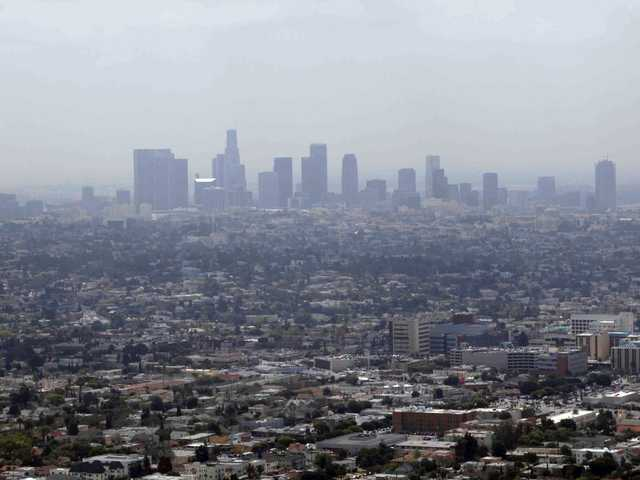 This April 28, 2009 file photo shows smog covering downtown Los Angeles. In its first major regulation since the election, the Obama administration will impose a new air quality standard that reduces the limit by 20 percent.
