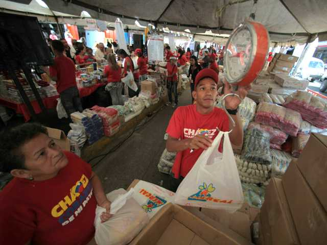 A worker weighs a bag of government subsidized food for a customer at a state-run market in Caracas, Venezuela.