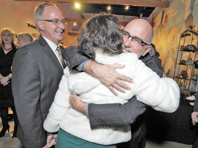 Patty Kolin embraces former city manager Ken Pulskamp as she and Jeff Kolin, left, congratulate him at his retirement party on Friday night at the Santa Clarita Activities Center.