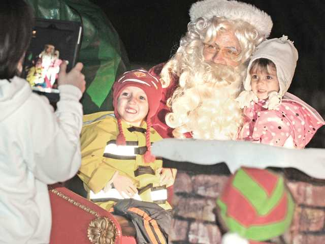 Elijah, 4, left, and Alexis Williams, 2, take a photo with Santa atop the Castaic Lions Club Santa Claus Christmas float as it makes a stop on San Remo Place in Castaic on Thursday night.