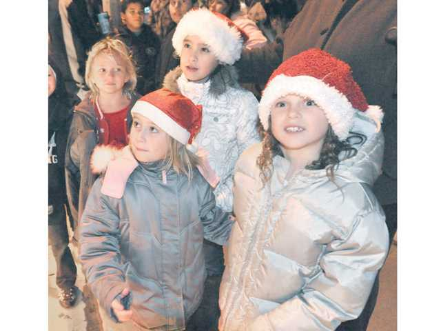 From left, Emily Kysar, 7, front, Maria Jauregui, 8, rear, and Savannah Lopata, 6, wait to sit on Santa's lap atop the Castaic Lions Club Santa Claus Christmas float as it makes a stop on San Remo Place in Castaic on Thursday night.