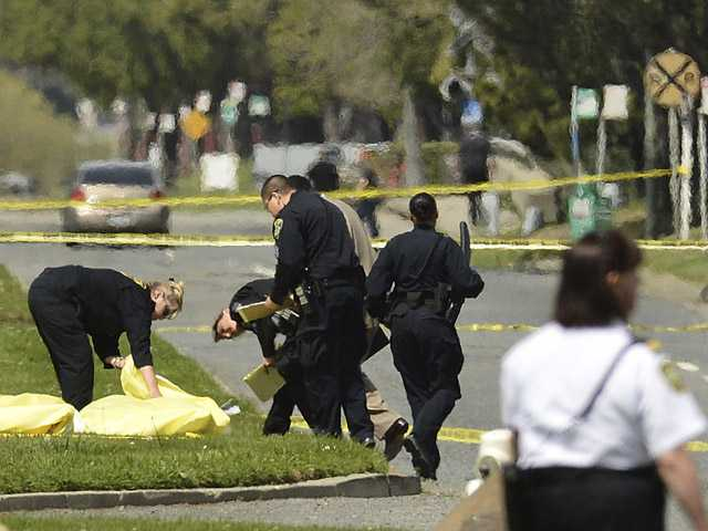 In this April 2 photo, Oakland Police cover the bodies of victims near Oikos University in Oakland, Calif.