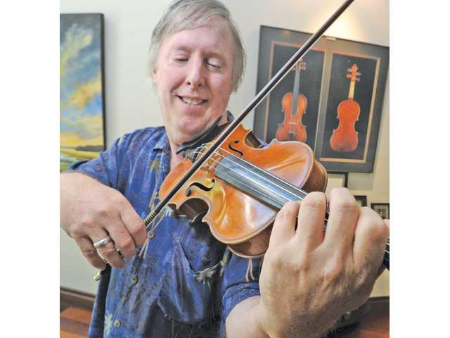 "David Ewart said the replacement for his 1765 Januarius Gagliano violin that was destroyed in the 2005 fire (pictured in a photo behind Ewart) ""found me."""