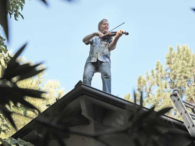 Professional violinist David Ewart survived an almost deadly house fire in 2005. Here he plays his violin on the roof of his rebuilt Valencia Hills home.