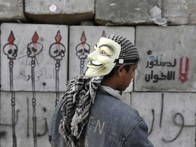 A protester looks at graffiti on cement blocks in front of the presidential palace in Cairo, Egypt.