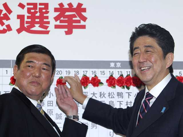 Shinzo Abe, right, of the Liberal Democratic Party, and the party Secretary-General Shigeru Ishiba pose for photos.