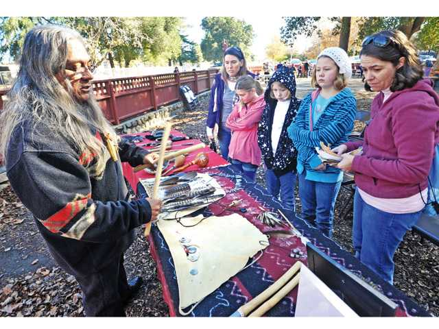 Dennis Garcia, left, displays Chumash crafts and tools he made in the traditional ways of his Native American ancestors for Girl Scout Troop 6412 in Newhall on Saturday.