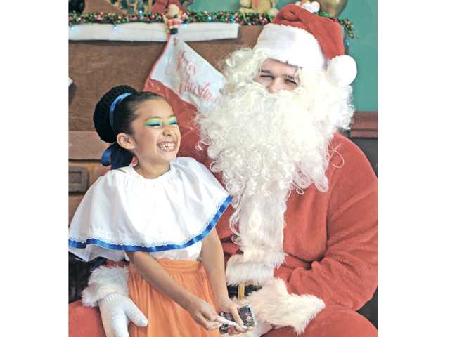 Nica Spargifiore as Mrs. Claus, right, guides Estrella Alejo, 6, over to meet Jonatahn Spargifiore as Santa at Heritage Junction in Newhall on Saturday.