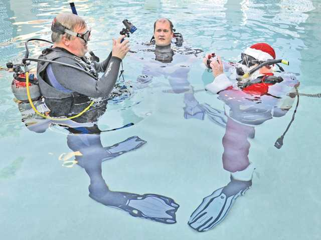 Scuba instructors Scott Page-Pagter, left, and Dave Wintermate, right, dressed as Santa, check their waterproof cameras as Jonathan Swanson, of Canyon Country, waits