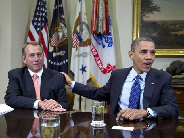President Barack Obama acknowledges House Speaker John Boehner of Ohio while speaking to reporters in the Roosevelt Room of the White House in Washington.