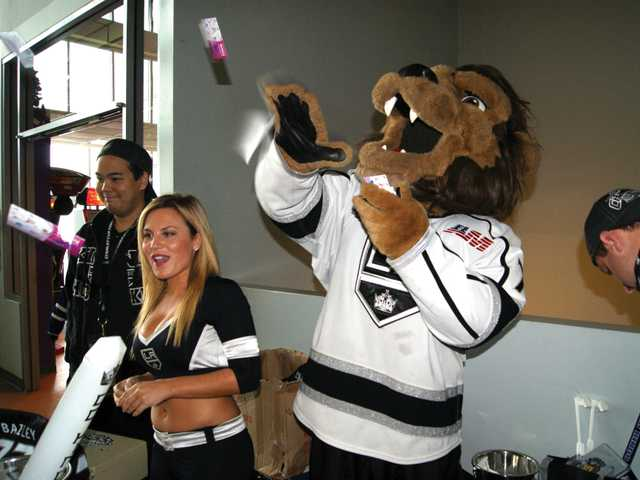Los Angeles Kings Ice Crew member Nikki Zager, left, helps the team's mascot, Bailey, throwing out promotional items to enthusiastic young Kings fans from the Santa Clarita Valley, during the LA Kings Ice Station Valencia Fan Fest on Sunday, at the rink near Valencia High School.