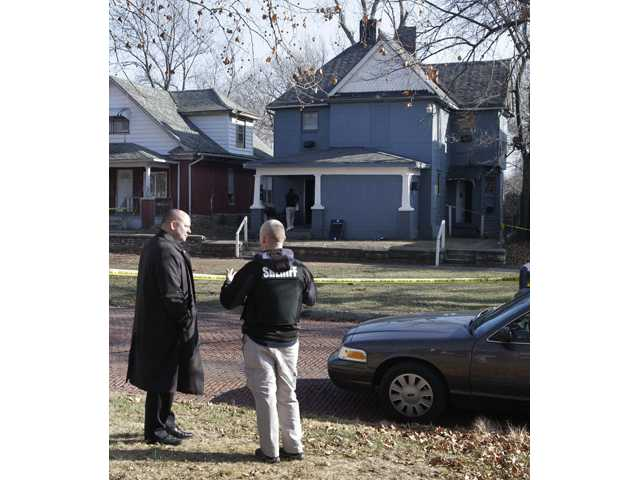 Investigators talks while standing across the street from a house where a man suspected of fatally shooting two police officers had stayed after the crimes.