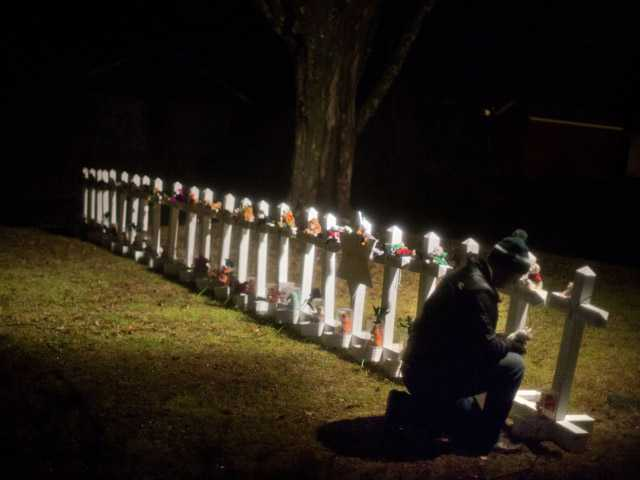 Frank Kulick, adjusts a display representing the victims of the Sandy Hook Elementary School shooting.