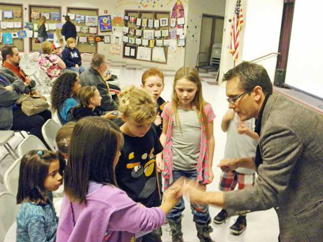 Magician Brian Hoffman, right, performed walk around magic for attendees of the Plum Canyon Elementary School Reflections celebration.