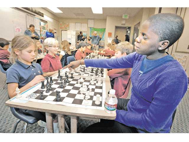 Ugandan chess champion Phiona Mutesi, right, points out a bad move by her opponent Ellery Potter, 6, during a chess demonstration as Mutesi visits with the Trinity Classical Academy Chess Club at Trinity Classical Academy in Valencia on Wednesday.
