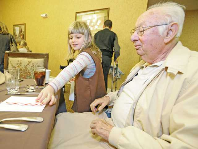 Kate Litton, 7, delivers a holiday card and candy cane to Fred Gross at Sunrise Senior Living in Valencia on Monday.
