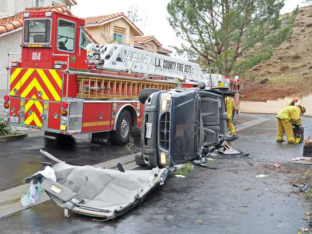 Firefighters work the scene of a single-car crash on Camelot Court near Shangri-La Drive in Canyon Country on Tuesday morning. (Jonathan Pobre/The Signal)
