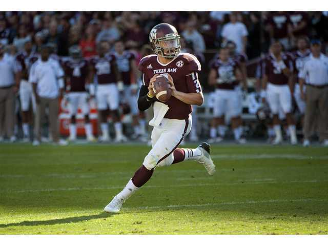 Texas A&M's Johnny Manziel rolls out to throw a touchdown pass on nov. 17 against Sam Houston State in College Station, Texas. On Tuesday, Manziel became the first freshman to be voted The Associated Press Player of the Year in college football.
