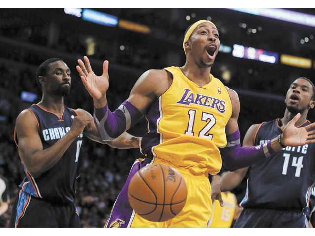 Los Angeles Lakers center Dwight Howard, center, celebrates his dunk between two Charlotte Bobcats defenders on Tuesday in Los Angeles. The Lakers won 101-100.