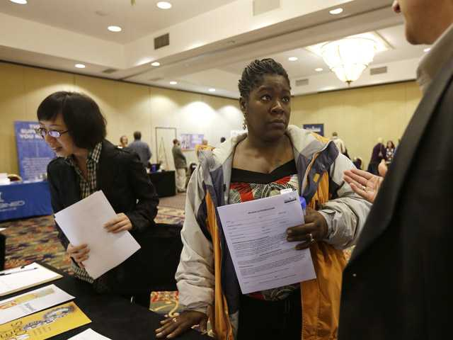 Angela Winters of Schenectady, N.Y., center, talks to a recruiter during a job fair at the Marriott Hotel on ,in Colonie, N.Y.