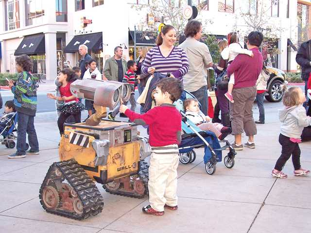 A child interacts with a life-size replica of the animated character Wall-E at the Celebrity Christmas Breakfast.