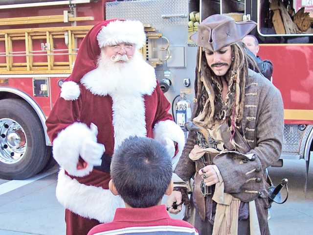 Santa is greeted by Jack Sparrow, right, and children.