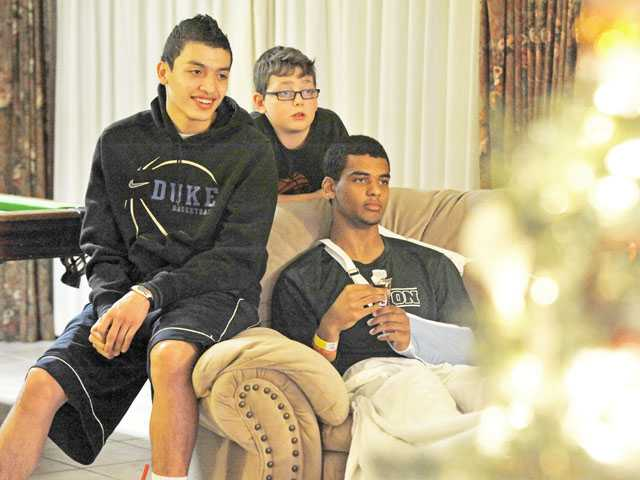 Dean Hendrix-Davis, right, watches television in his Newhall home Wednesday with Canyon High teammate Marc Cabrera, left, and brother Will Gillinger, 9.