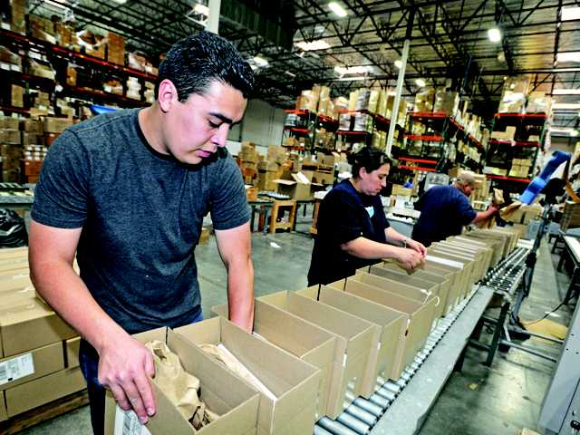 Francisco Aguilar, left, and Felipa Molina-Gomez prepare shipments of TOMS shoes at one of AMS Fulfillment's warehouses in Valencia on May 9, 2011.