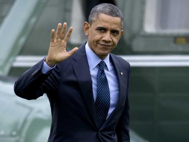 President Barack Obama waves to the media as he walks from Marine One to the Oval Office of the White House on Thursday in Washington, as he returns from Walter Reed National Military Medial Center in Bethesda, Md., where he visited injured military members.