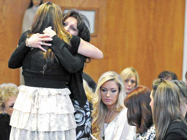 Sandy Richard, left, and Sherri DeMott, mother of Dakota DeMott, embrace at St. Clare Catholic Church in Canyon Country on Jan. 18.