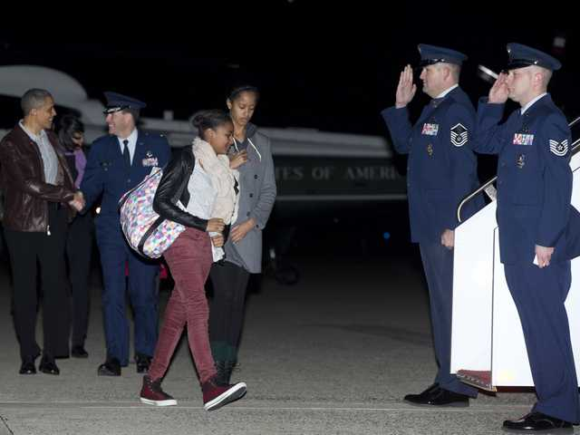 President Barack Obama, First Lady Michelle Obama and their daughters Malia and Sasha walk from Marine One to board Air Force One, Friday, in Andrews Air Force Base, Md., en route to a holiday vacation in Honolulu.