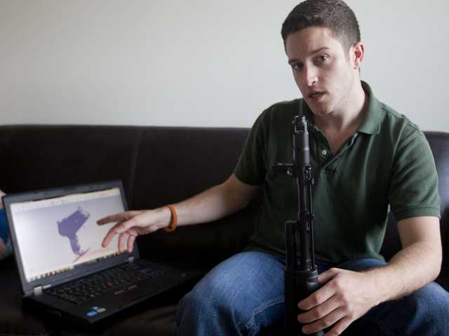 "In this Oct. 3 photo, ""Wiki Weapons"" project leader Cody Wilson points to his laptop screen displaying an image of a prototype plastic gun on the screen, while holding in his other a weapon he calls ""Invivdual Mandate,"" in Austin, Texas."