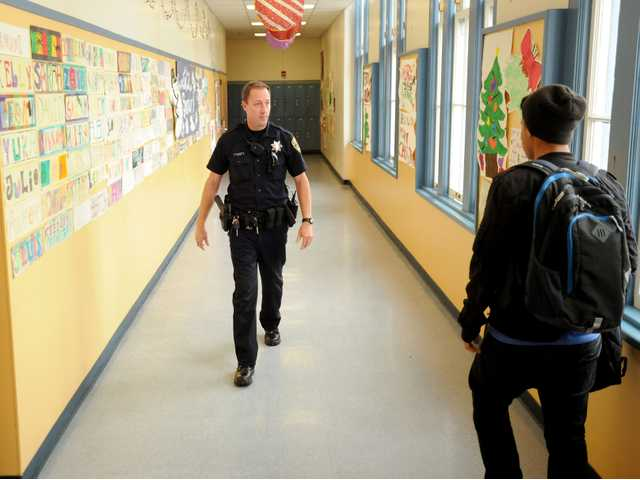 In this Dec. 17 photo, Officer Rick Moore of the Oakland school district police patrols Oakland Technical High School in Oakland.
