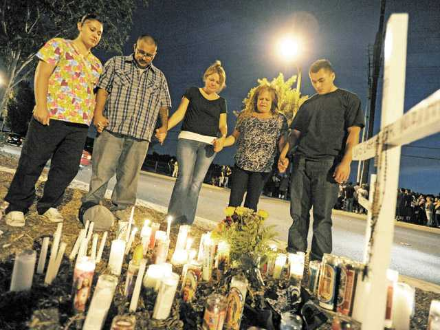 Close friends of Luis Castillo pray around a makeshift memorial at the spot where he was killed in an automobile crash, on Soledad Canyon Road west of Camp Plenty Road in Canyon Country on July 13. From left, Mayra Prial, Gregorio Prial, Denise Reeves, Dory Aase and David Aase.