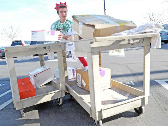 Ryan Pederson, of Stevenson Ranch, stacks packages to be sent to needy families in Castaic on Friday. (Jonathan Pobre/ The Signal)
