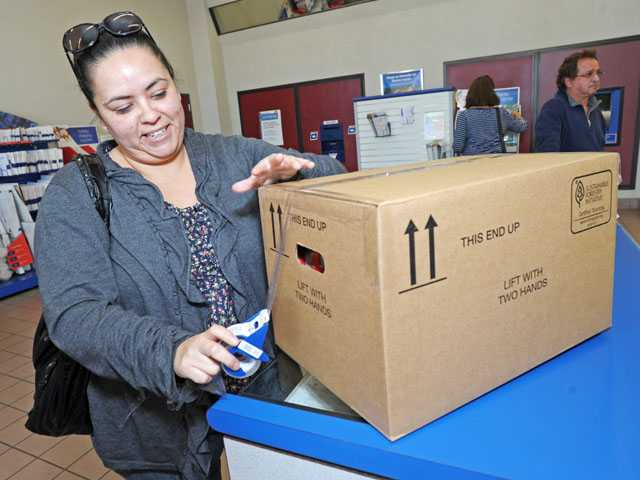 Patty Ramirez, of Oxnard, prepares a package for needy families she adopted in the U.S. Postal Service's Letters to Santa program on Friday.(Jonathan Pobre/ The Signal)