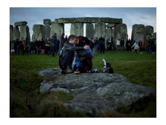 People embrace by the ancient stone circle of Stonehenge, in southern England, as access to the site is given to druids, New Age followers and members of the public on the annual Winter Solstice, Friday, Dec. 21, 2012. According to legend, the ancient Mayans' long-count calendar ended at midnight Thursday, ushering in the end of the world.