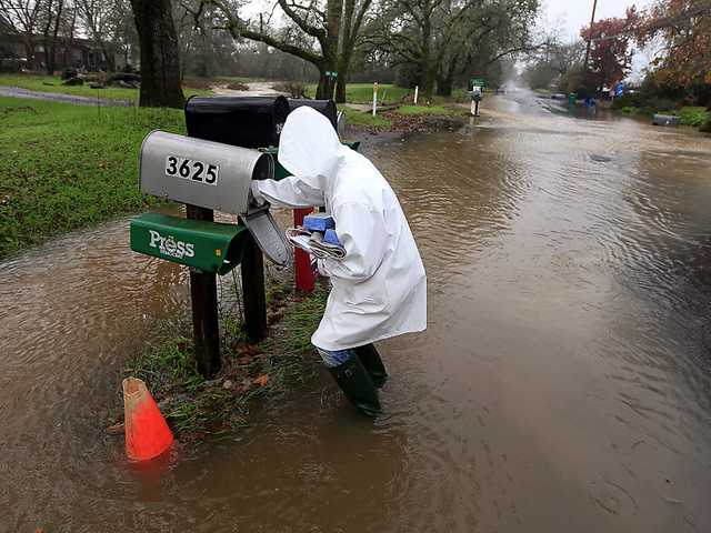 Sandy LeDuc braves floodwaters to gather her mail on Piner Road, Friday in Santa Rosa as a large winter storm barreled in to Northern California.