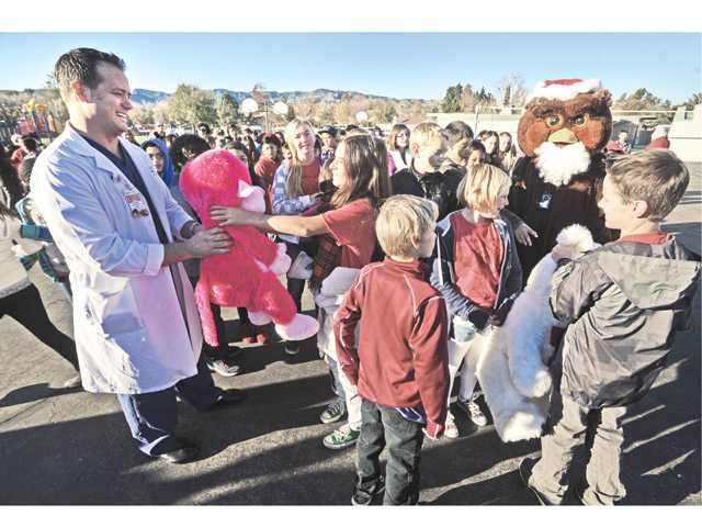 Dr. Darin Privett of the Emergency Department at Henry Mayo Newhall Memorial Hospital accepts two stuffed animals from students at Old Orchard Elementary School in Valencia on Friday. School mascot Oliver the Owl, right, looks on.