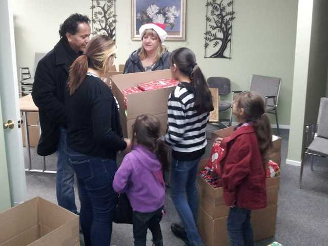 A family in Val Verde receives gifts donated by AMS Fulfillment employees.