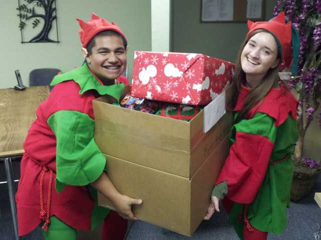 AMS Fulfillment elves Raul Domrique, left, and Sarah Cope, play elves during the holiday event held at the Val Verde Community Center.