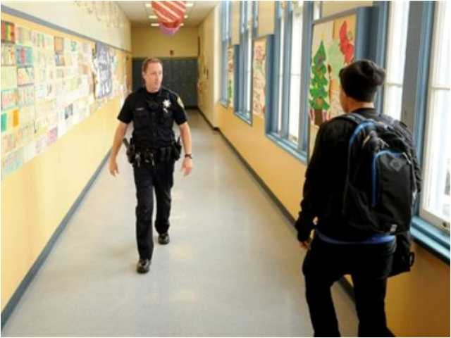 Officer Rick Moore of the Oakland school district police patrols Oakland Technical High School in Oakland, Calif. The National Rifle Association on Friday, Dec. 21 2012 called for the placement of an armed police officer in every school.