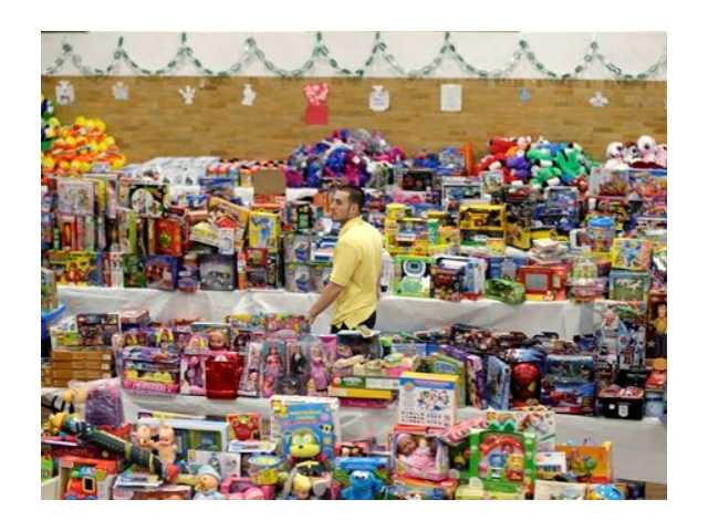 Volunteer Anthony Vessicchio of East Haven, Conn., helps to sort tables full of donated toys at the town hall in Newtown, Conn., Friday, Dec. 21, 2012.